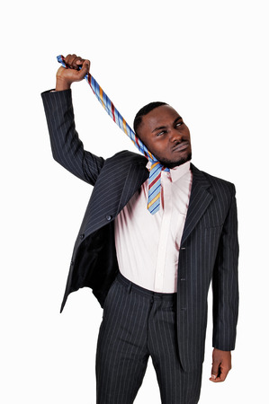 A serious young black businessman pulling on his necktie, in a suit  photo