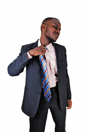 A smiling young black businessman taking off his necktie, in a suit forwhite background  photo