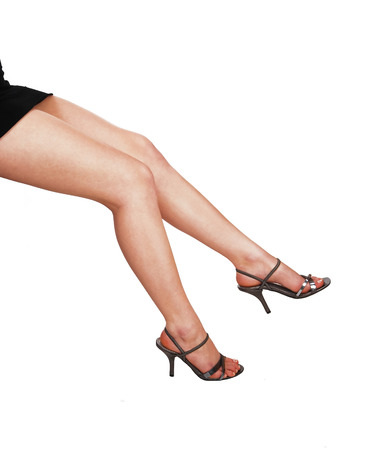 The legs of a young woman in high heels, sitting for white   Stock Photo