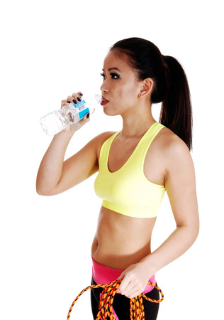 A young slim Chinese woman in an exercise bra standing for whitebackground drinking water from a bottle  photo