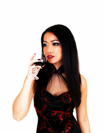 tradition: A very pretty slim Chinese woman in a long Chinese dress drinkinga glass of red wine for white background