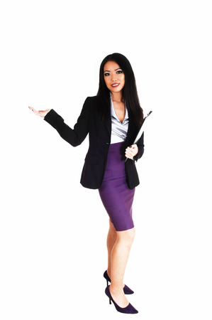 A beautiful young slim Asian business woman in a black jacked andlilac skirt with long black hair standing for white background  photo