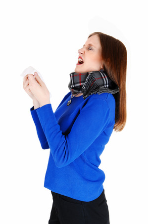 winter woman: A young woman with a heavy scarf around her neck holding a tissue andsneezing, for white background  Stock Photo
