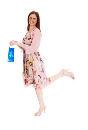 A beautiful young woman in a summer dress standing on one leg holdinga blue shopping bag for white background  photo