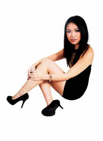 A pretty and slim young Chinese woman in a short black dress sittingon the floor for white background  photo