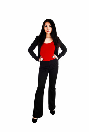A beautiful young slim Asian business woman in a black jacked anddress pants with long black hair standing for white background