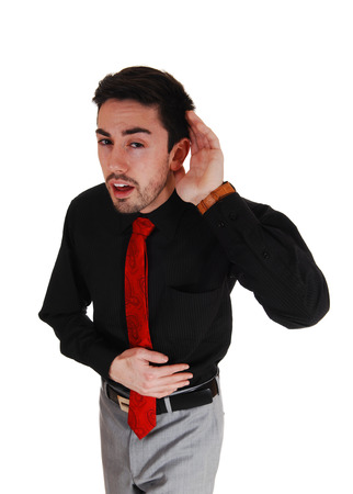 A young businessman holding his hand behind his ear, he can not hearto good, isolated for white background  photo