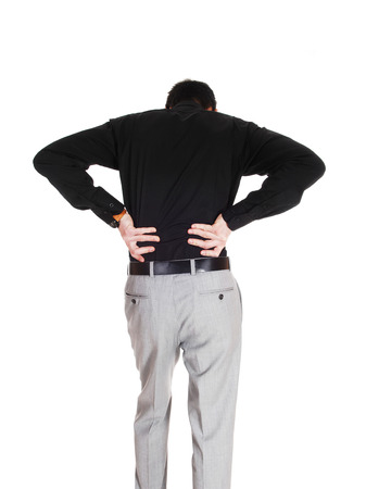 A young businessman standing from the back holding his hands onhis back for heavy back pain, isolated for white background  photo