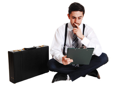 A young business man sitting on the floor looking on his notes with hisbriefcase beside him, isolated on white background  photo