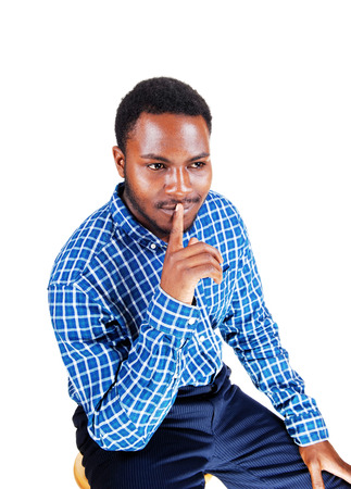 A handsome young black man in a blue shirt with one finger on hismouth, sitting isolated for white background  Stok Fotoğraf
