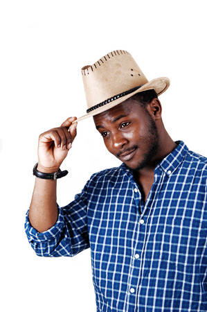 A smiling young black man in a blue shirt and an cowboy hat on his headstanding isolated for white background  photo