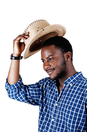 A handsome black man in a blue shirt lifting his cowboy hat and smilingisolated for white background  photo