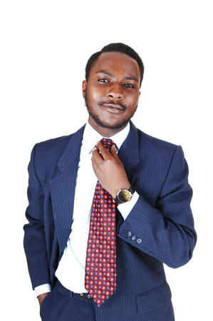 A young black business man standing in a blue suit and tie, fixing his tiefor white
