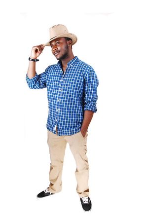 A handsome black man in a blue shirt lifting his cowboy hat and smilingisolated for white  photo