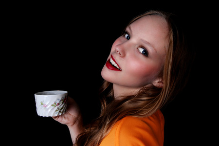 mujer tomando cafe: Una hermosa adolescente con una taza de café y sonríe