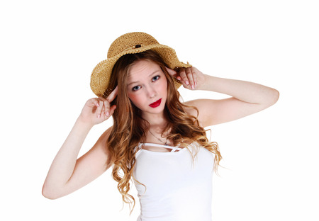 A lovely young woman with long curly blond hair wearing a beige strawhat, isolated for white background  photo