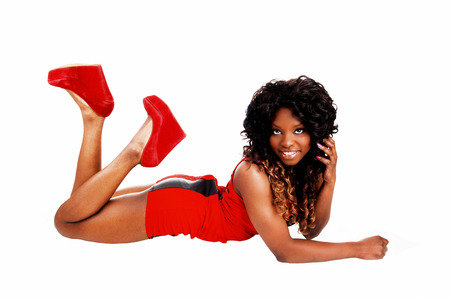 curls: A pretty Jamaican woman in a red short dress and long curly hair lyingfor white background on the floor