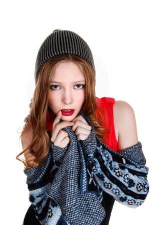 A young woman in a blue-grey sweater and knitted hat, isolated forwhite background  Фото со стока