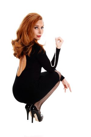 A happy woman in a black dress and long brunette hair crouching onthe floor, isolated for white background  photo