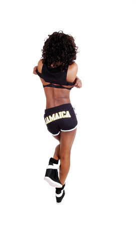 A pretty Jamaican woman in exercise outfit with her longblack and brown hair standing from the back, isolated for white background  photo