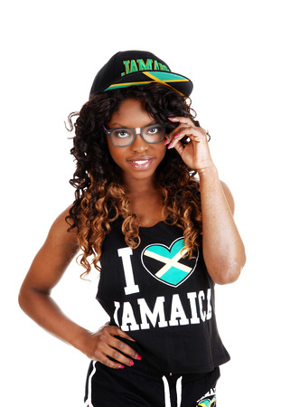 A pretty Jamaican woman in exercise outfit and a cap on her longblack and brown hair standing isolated for white background  photo