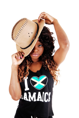 A pretty Jamaican woman in exercise outfit and a cowboy hat on her longblack and brown hair standing isolated for white background  photo