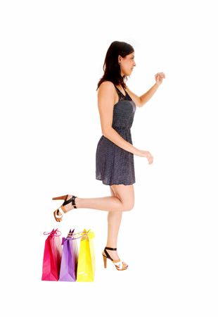 shoppingbag: A young pretty woman in a grey dress standing beside her three shoppingbag