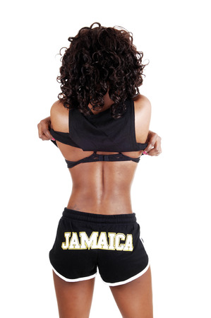 A pretty Jamaican woman in exercise outfit taking of her top, withblack and brown hair standing isolated for white background  photo