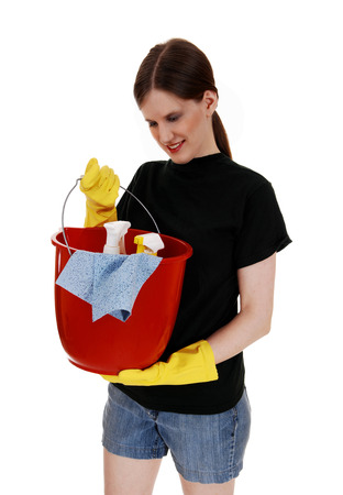 A young woman in shorts and yellow rubber cloves holding up an redbucket ready for cleaning, for white background