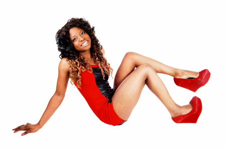 jamaican adult: A lovely Jamaican young woman in a short red dress, with her curly blackhair sitting on the floor, isolated on white background