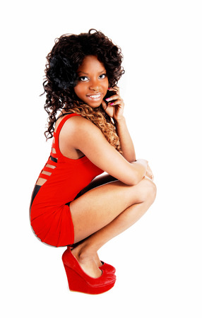 jamaican adult: A lovely Jamaican young woman in a short red dress, with her curly blackhair crouching on the floor, isolated on white background  Stock Photo