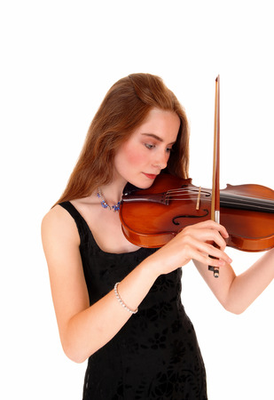 A young pretty woman with long brunette hair standing isolated for whitebackground and playing the violin