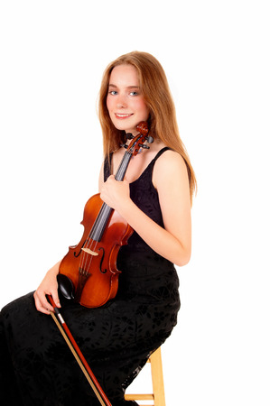 A pretty woman in a black dress sitting and holding her violin, smilinginto the camera, isolated for white background  photo