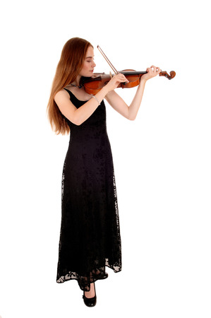 A slim young woman in a long black dress standing for white backgroundplaying the violin  photo