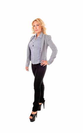 A full size picture of a beautiful blond young woman in a grey blouse andjacket, isolated on white background  Stock Photo