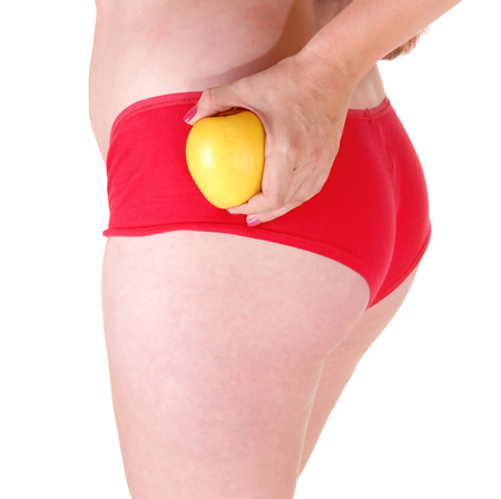 A closeup picture of the bottom of a woman in red panties, holding aapple, isolated on white background  photo