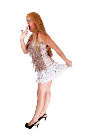 falda corta: Una mujer alta y rubia que parece muy sorprendido, en su falda corta, isolatedover fondo blanco.