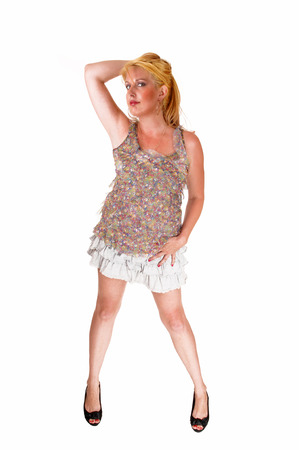 falda corta: Una mujer, alta y con largo pelo rubio pie en una falda corta, isolatedover fondo blanco. Foto de archivo