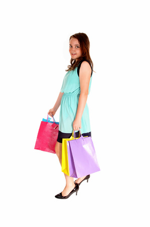 A lovely young teen girl caring several shopping bag