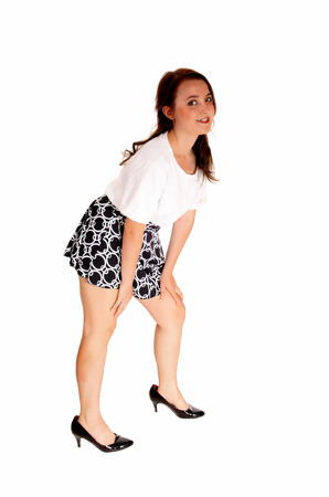 A pretty teenager girl in a white blouse and short skirt standing isolatedfor white background, bending down.