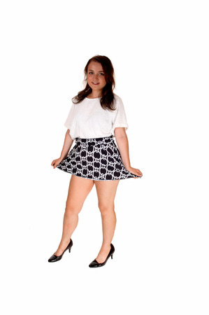 A full length picture of a pretty teenager girl in a white blouse and shortskirt standing isolated for white background.