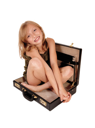 A lovely little girl with blond curly hair sitting in a black open briefcase,isolated on white background.