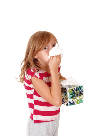 running nose: A lovely young blond girl holding a tissue on her running nose,isolated for white background.