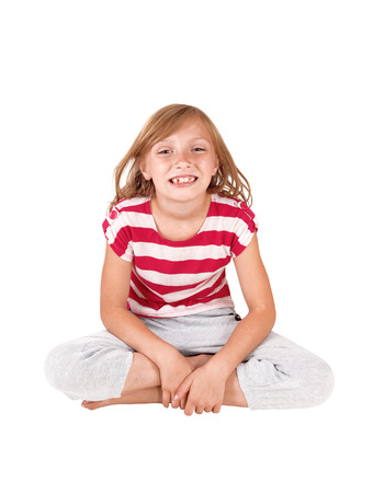 A very happy young girl sitting smiling on the floor in the studio,isolated on white background.
