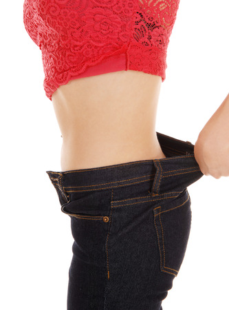 A young woman standing in profile, showing her weight loss in her jeans isolated on white background. photo