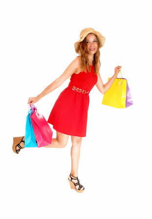 shoppingbags: A beautiful young woman in a red dress, running with her shopping bags, wearing a beige hat, isolated for white background.