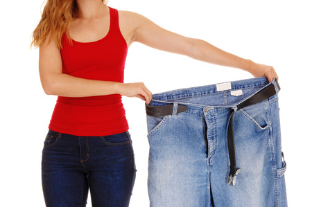 A young slim woman in jeans holding her old big jeans after she lost much weight, isolated for white background.