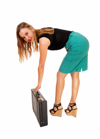 bending down: A beautiful young business woman bending down to her briefcase, wearing a green skirt and black blouse, isolated on white background. Stock Photo