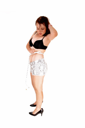 A full body picture of a young woman in shorts and a black bra standing forisolated for white background measuring her waist. Imagens