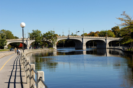 rideau canal: An old stone bridge over the Rideau canal on Ottawa Canada undera blue sky.